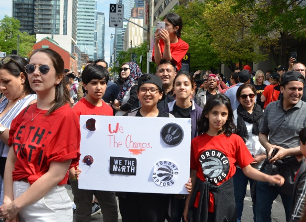 Raptors fans, parade day, a group of kids with a hand made sign that says we the champs with pasted on pictures of raptors symbols