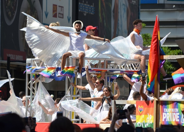 people draped in white with large white fabric wings sitting on top of a float in the pride parade