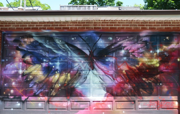 a very large butterfly on a mural on a grage door, wild colours in blues and red, It looks like the butterfly is superimposed on the whole universe