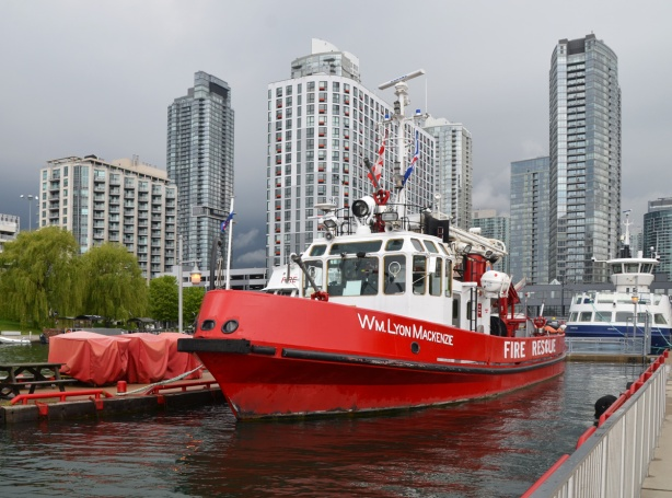 The WIlliam Lyon McKenzie, a bright red fire boat is docked at Toronto waterfront, city skyline behind the boat with tall condos, also dark storm clouds