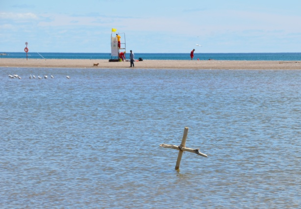 water behind the lifeguard station, Woodbine Beach, someone has put a cross made of two branches lashed together
