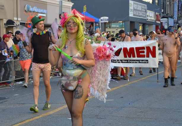 person with long yellow wig and sunglasses, walkin in parade in front of a group of naked men. Also a tall skinny man with a green hat and pink shorts