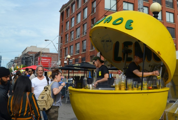 a big yellow sphere open in the middle, a drink stand, serving lemonade to people at Taste of Little Italy street festival