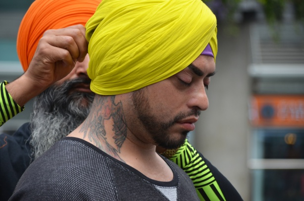 an older man with a beard and an orange turban, is tying a yellow turban onto the head of another man who has a large tattoo on his neck