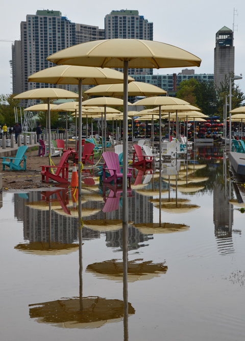 Toronto waterfront showing flooding at H 2 O park with its Muskoka chairs and yellow umbrellas, many colourful reflections in the flood waters