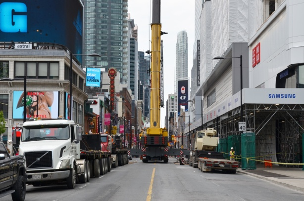 a large crane is on a truck in the middle of Yonge street, downtown, with tall buildings on both sides including the Eaton Centre under renovation on the right
