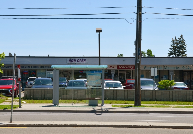 looking across the street to a bus shelter that is in front of a strip mall with cars parked in front of the stores