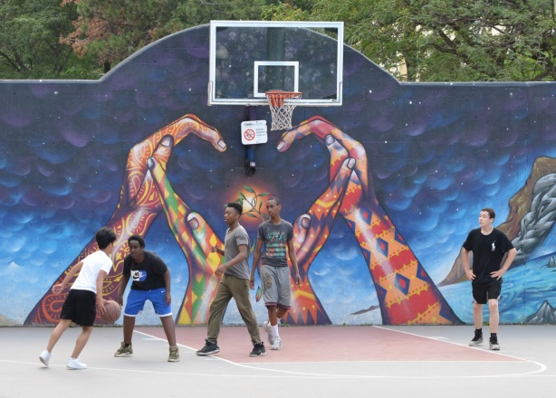 a group of boys playing basketball on a court that has a mural of two hands forming a heart shape with their hands, the heart is under the basket, mural is on wall