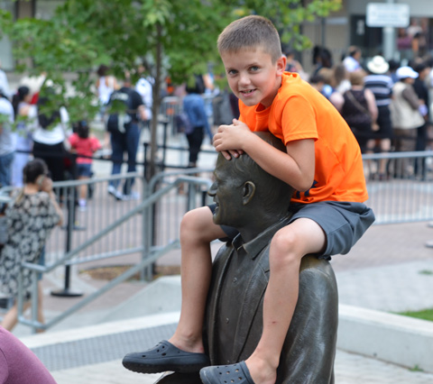 a boy in an orange T-shirt, grey shorts, and black crocs sits on the shoulders of Jack Layton sculpture by the ferry terminal, holding onto Layton's head, and smiling at the camera