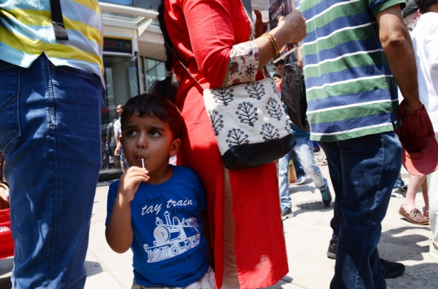 a small boy stands behind his mother, he's wearing a blue t shirt and has a lollipop in his mouth