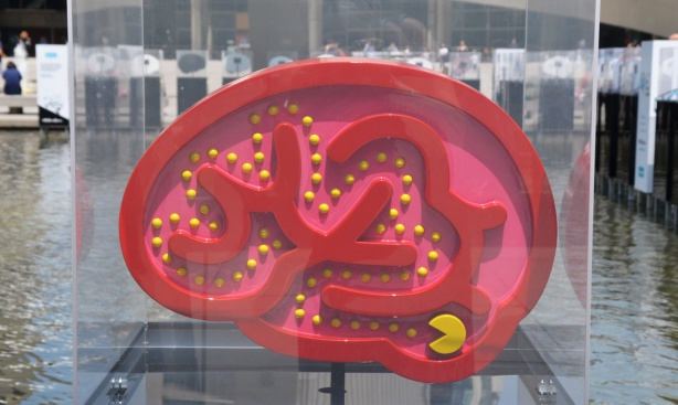 a brain shaped 2 dimensional sculpture, red, made to look like a pac man arcade game, yellow pac man gobbling up yellow dots by Orit Fuchs