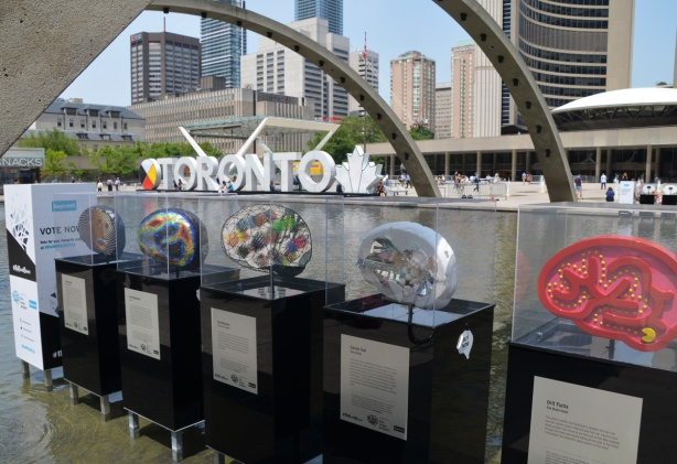 brain shaped sculptures on display, with the 3 D Toronto sign and Toronto city hall in the background