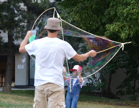 a young boy breaks a very large bubble that a man has made, outdoors