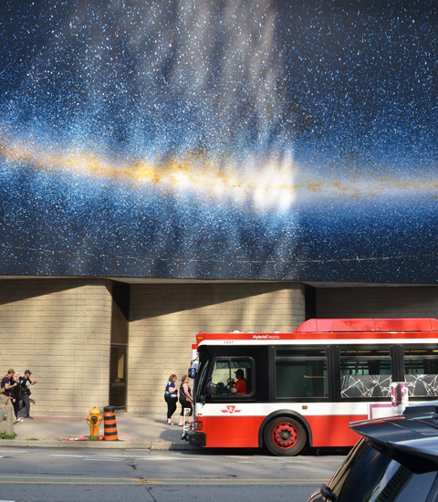 a red and white TTC bus stops beside a concrete building with a very large photograph pubic art installation on the upper part of the building,