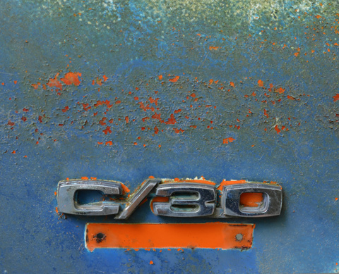 an old C/30 badge from a blue vehicle, with orange underneath