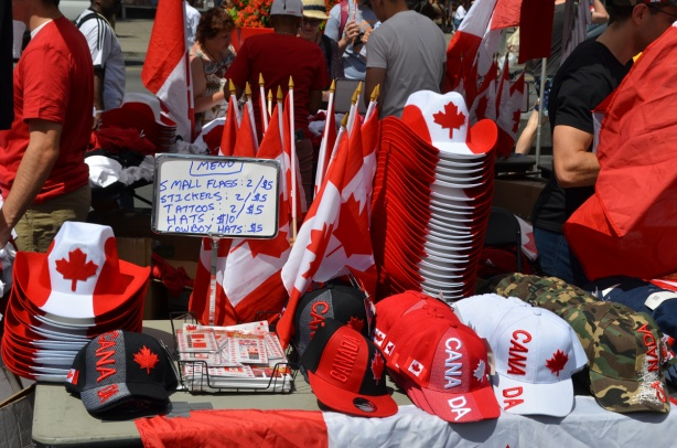 on a table outside, piles of Canada Day merchandise for sale, hats, cowboy hats, flags, etc