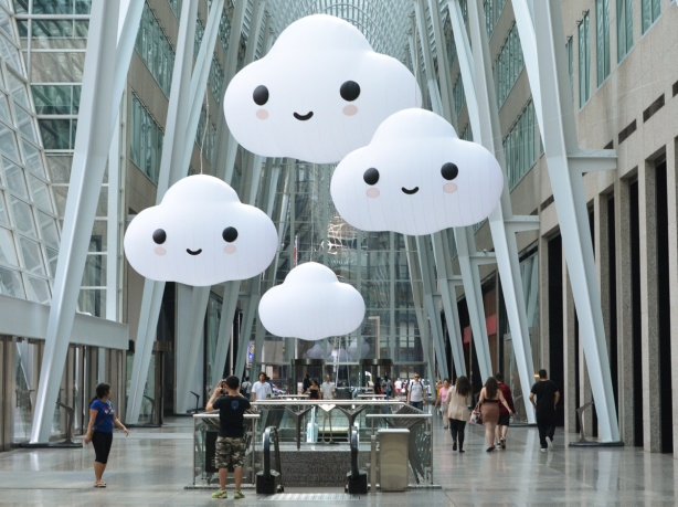 art installation in Brookfield Place of 4 large white clouds, three of which have happy faces on them, suspended from the ceiling over the escalator from the lower level,