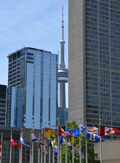 the CN Tower peaks out between two tall buildings, in front are Canadian flags and flags from all the provinces