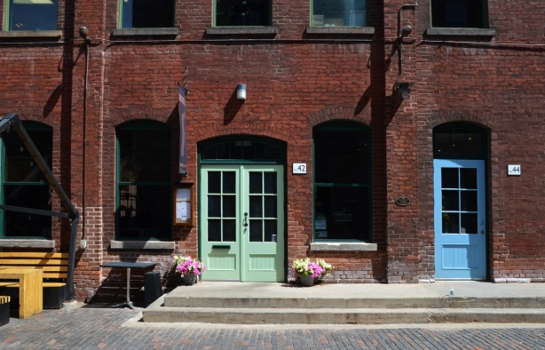 distillery district, brick building with doors painted in light green and light blue