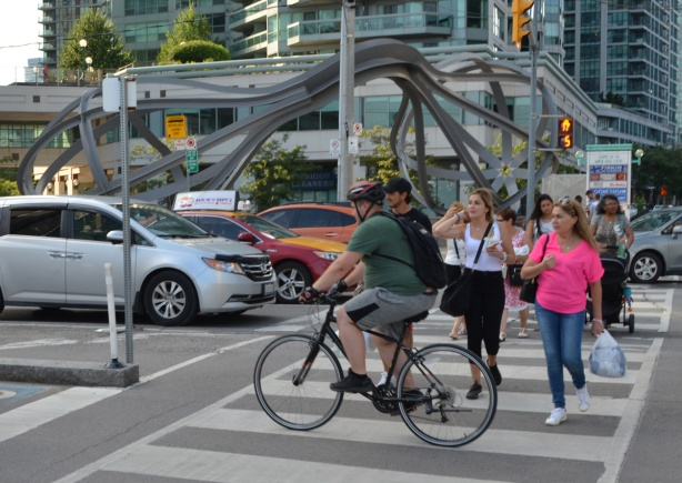 cars, cyclists, and pedestrians at an intersection