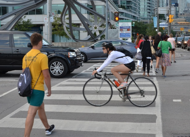 woman on a bike cycles through a red light at Yonge and Queens Quay