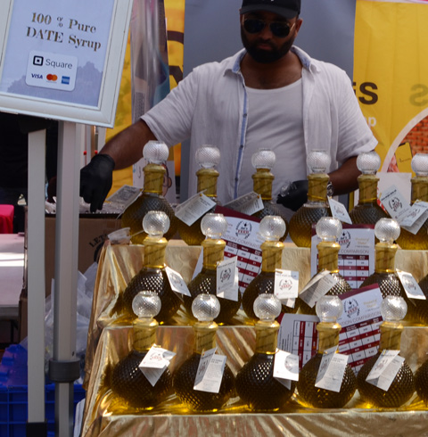 a man stands behind a display of bottles of date syrup that are for sale at an outdoor event
