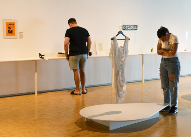 a man and a woman looking at objects and reading the stories on display at the museum of broken relationships