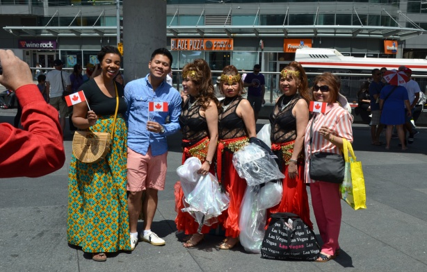 a group having their picture taken at Yonge Dundas Square, one Asian man and four women. Three women are in costume as they are about to perform on the stage in that square, Canada Day celebrations