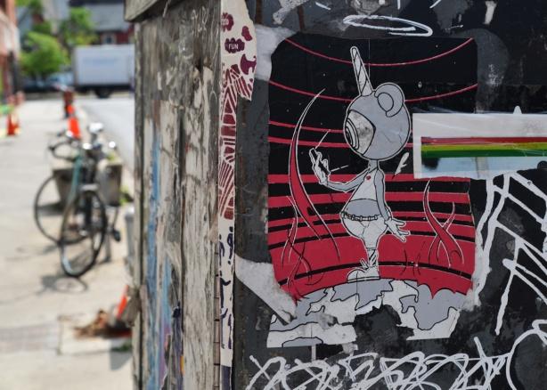 sticker on a grey box on sidewalk, little figure, martian alien like, with head mostly one eyeball, human shape,