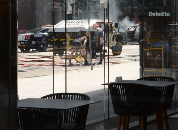 looking through the window of a restaurant with two empty tables, to a scene where a film set is setting up to shoot a scene involving exploding buses and police cars