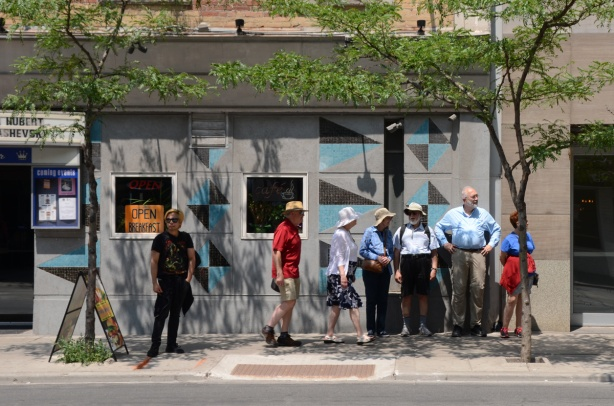 a group of older men and women in sun hats stands in a bit of shade cast by a little tree outside the Rex on Queen Street West