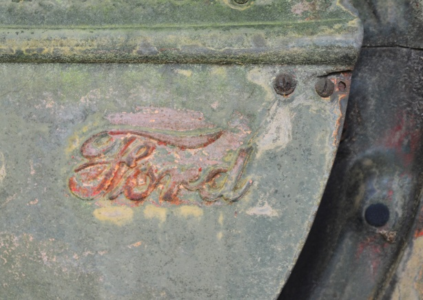 old Ford badge on side of junked car or truck