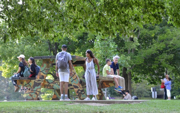 a group of people sit on an oversized picnic table painted in camo colours in a park