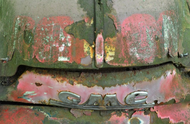 front of an old GMC vehicle, green with pink and yellow patches