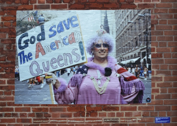 a large picture attached to a brick exterior wall, a person in lavender coloured dress and big grey wig holds a sign that says God save American queens