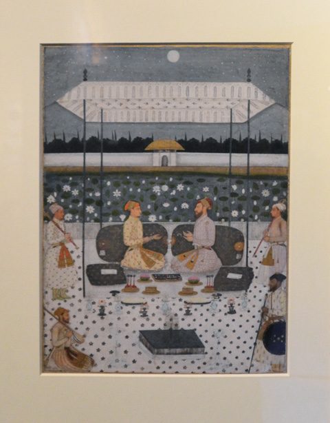 illustrated page of an old book depicting people sitting in a moonlit garden in India, two men on cushions