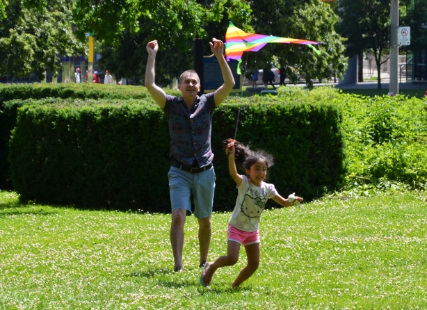 a young girl runs with a kite that her father has just let go of