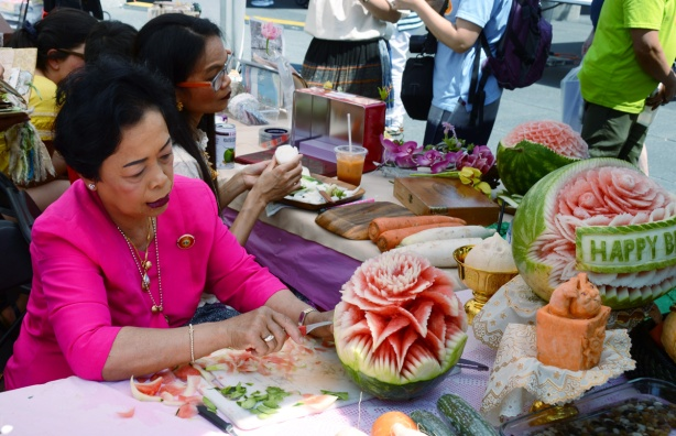 an older Thai woman is making an intricate carving from a watermelon