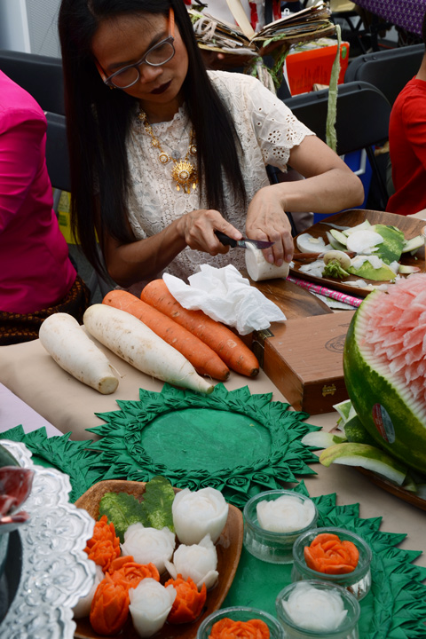 a woman is carving carrots and another white vegetable into flowers