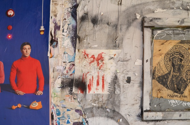 parts of a few different posters and drawings on a wall, a man in a red shirt on blue background which is part of an ad is on the left, a drawing of three naked women is in the middle (but is faint and hard to see), and a drawing on yellow labelled knowledge