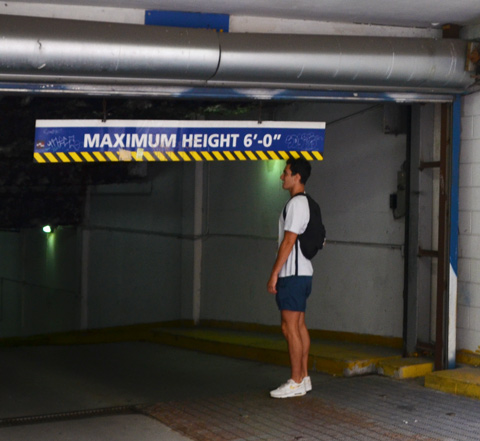a young man stands by a maximum height 6 feet sign at the entrance of a parking garage, to see if he is 6 feet tall
