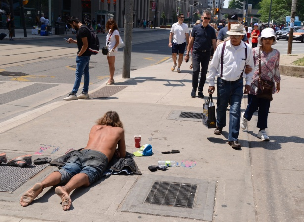 a man with no shirt and bare feet lies on the sidewalk surrounded by some of us stuff, people walking past him