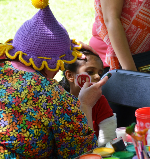 a woman in a purple and yellow clown hat apples a red maple leaf Canadian flag face paint on a girl's cheek