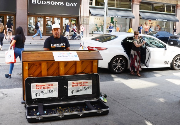 Mellow Dee, a male musician, plays the piano outside Eaton Centre on Queen street as a woman gets out of a white taxi behind him