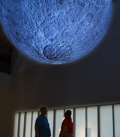 two people stand under a large model of the moon