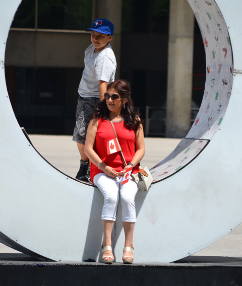 a mother and son pose in one of the o's in 3 D Toronto sign at Nathan Phillips. Mother is dressed in red and white and is holding two small Canadian flags