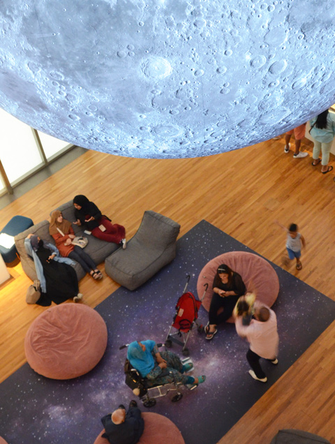 a groupof people sit on bean bag chairs under a large model of the moon, and on a carpet that looks like the night sky with stars