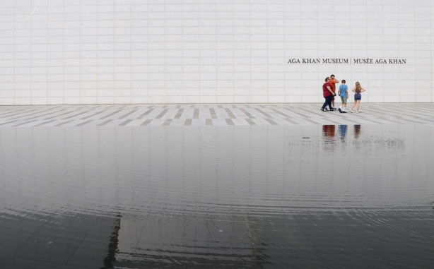 a group of people walk past the front of the white wall of the Aga Khan museum, between the museum and the reflecting pool