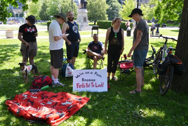 a group of people on the grass at Queens Park, with a sign that says we are having a picnic because Doug Ford is out to lunch