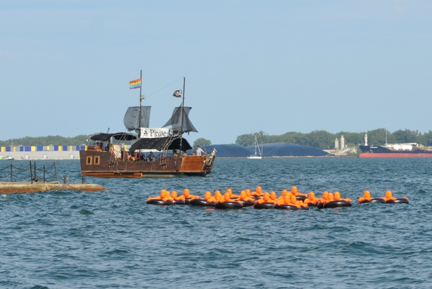 a pretend pirate ship, as a harbour cruise boat passes by the public art installation, SOS, or Safety Orange Swimmers